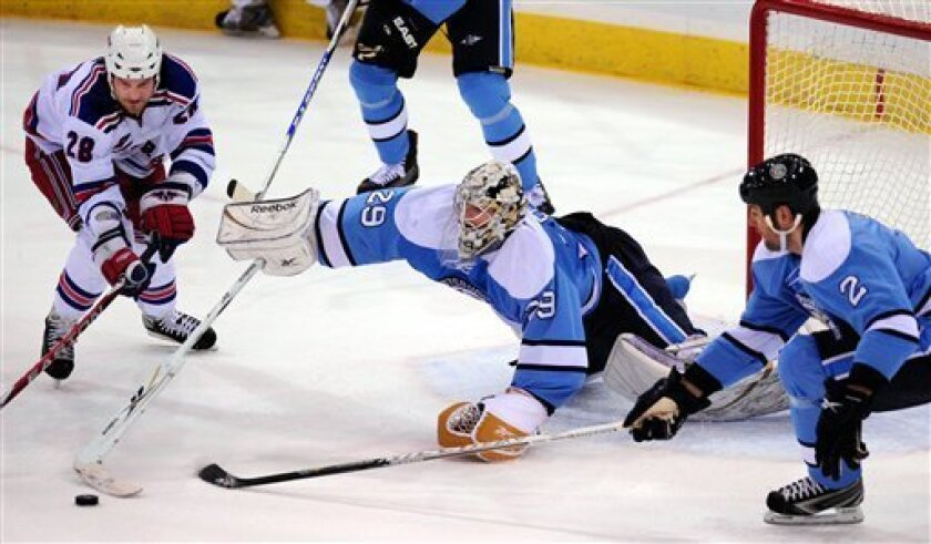 Pittsburgh Penguin goalie Marc-Andre Fleury, center, blocks a shot on goal by New York Rangers Colton Orr's, left, with an assist by Penguin's Hal Gil, right, during the second period of an NHL hockey game at Mellon Arena in Pittsburgh, Sunday, January 18, 2009. (AP Photo/John Heller)