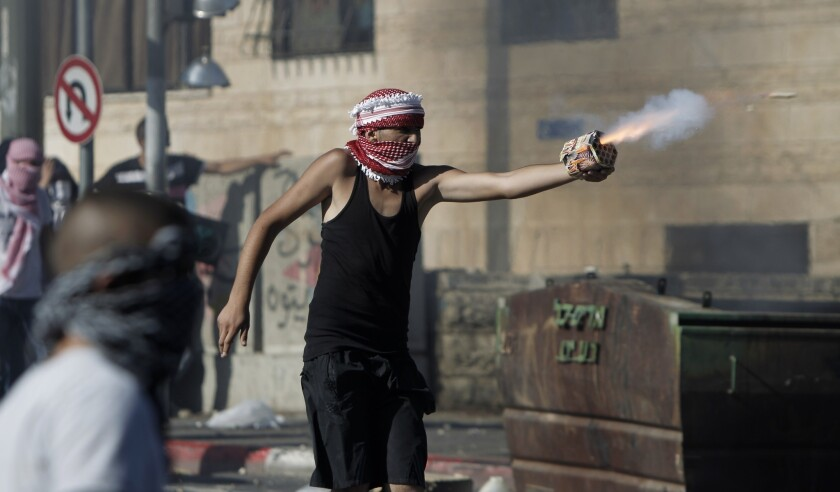 A Palestinian protester directs fireworks toward Israeli police during clashes in East Jerusalem following news of a feared reprisal killing for the deaths of three kidnapped Israeli youths.