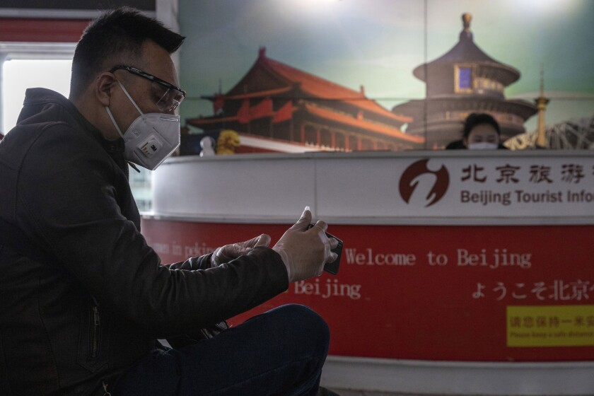 In this March 12, 2020, photo, a traveler waits near a tourist information booth at the Capital International Airport terminal 3 in Beijing. As the number of new cases dwindles in China and multiplies abroad, the country once feared as the source of the COVID-19 outbreak is now worried about importing cases from abroad. China hasn't imposed any travel bans, but Beijing said this week that all people arriving from overseas would have to self-quarantine for 14 days. (AP Photo/Ng Han Guan)