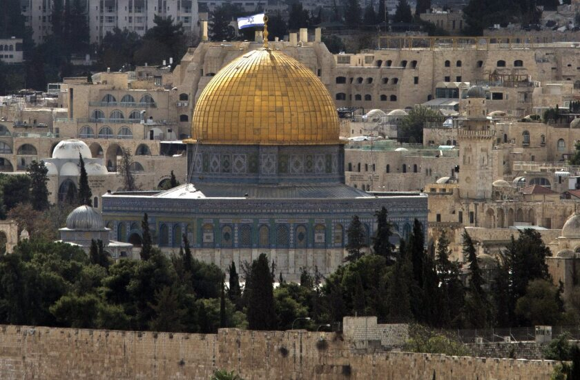 Seen from Mount Scopus, the distinctive golden Dome of the Rock, one of Islam's holiest sites, stands out in Jerusalem's walled Old City on Nov. 3. Behind it, a large Israeli flag flies atop an apartment building.