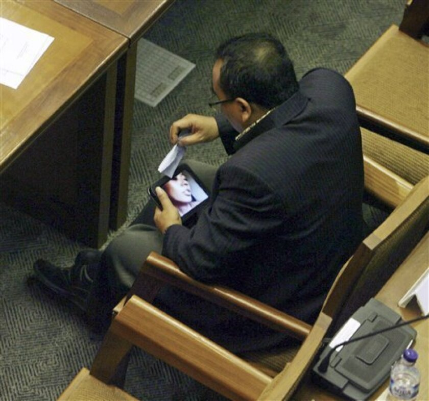 In this photo taken on Friday, April 8, 2011, Indonesian parliament member from Prosperous Justice Party (PKS) Arifinto watches a porn video on his tablet computer. The conservative lawmaker who helped pass a controversial anti-pornography law resigned Monday, April 11, 2011 after he was caught watching explicit videos on his computer during a parliamentary session. (AP Photo/Media Indonesia, M. Irfan) MANDATORY CREDIT, NO ARCHIVE, NO SALES