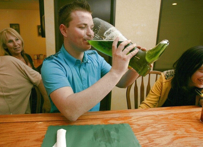 "Andrew Pomery, 24, of La Mesa tips back a 112-ounce green Pabst Blue Ribbon ""Das Boot"" at Centifonti in La Mesa."