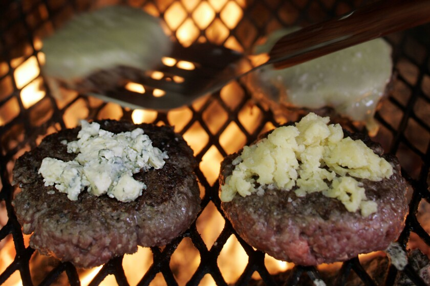 "FIRE IT UP: Silverton tops patties, made of beef with at least 20% to 28% fat, with crumbled chunks of blue cheese, left, and cheddar. ""With lean meat,"" she says, ""the burgers don't hold together."""