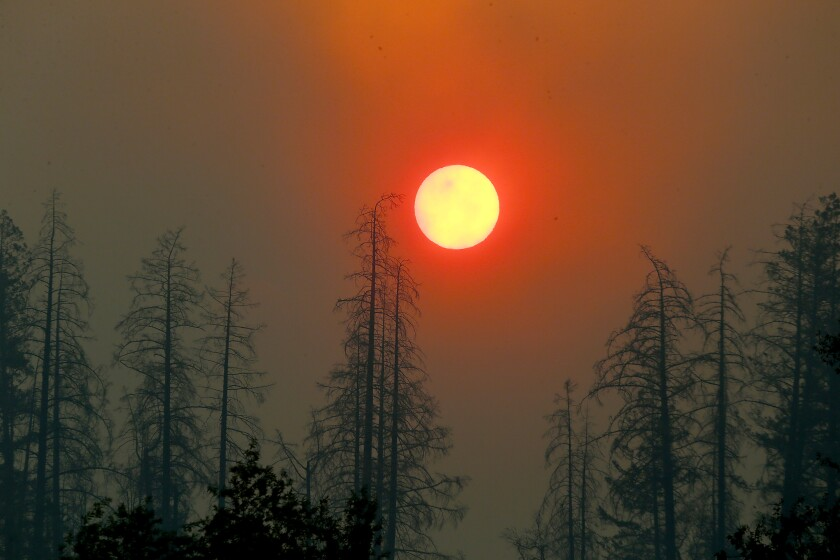 Smoke from the Kincade fire partially obscures the sun as it rises above Chalk Hill Road near Healdsburg, Calif., on Sunday.
