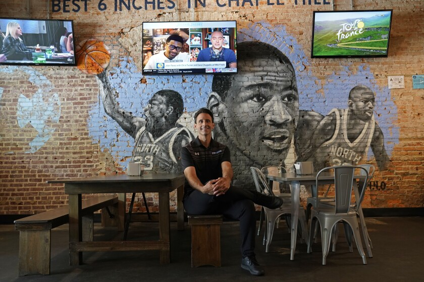 Bret Oliverio poses at his Sup Dogs restaurant in Chapel Hill, N.C., Thursday, July 15, 2021. Oliverio wants to pursue deals with college athletes to endorse his restaurant specializing in hot dogs and burgers along the main Franklin Street drag steps from the University of North Carolina. Like other small-business owners in college towns, he has to sort out what that entails with athletes free to profit from use of their name, image and likeness (NIL) for the first time. (AP Photo/Gerry Broome)