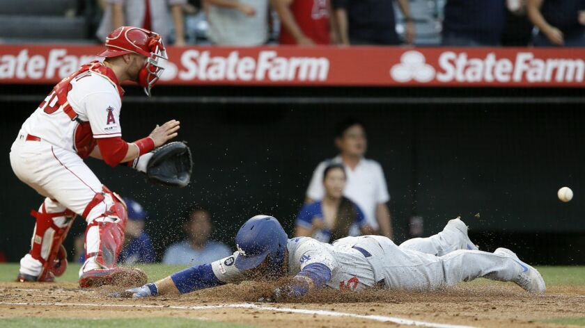Los Angeles Dodgers' Russell Martin, right, beats the throw from left field to Los Angeles Angels ca