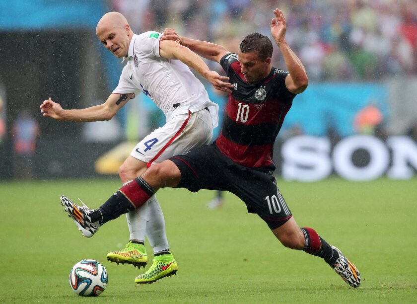 "Michael Bradley, left, battling Germany's Lukas Podolski during during a World Cup group game, says of the MLS that ""after almost 20 years we can all agree that to take this league where everyone wants to take it, changes need to be made."""