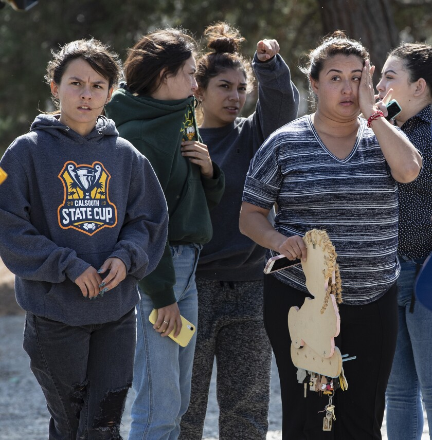 Residents wait after fleeing their home during a fire in Fontana