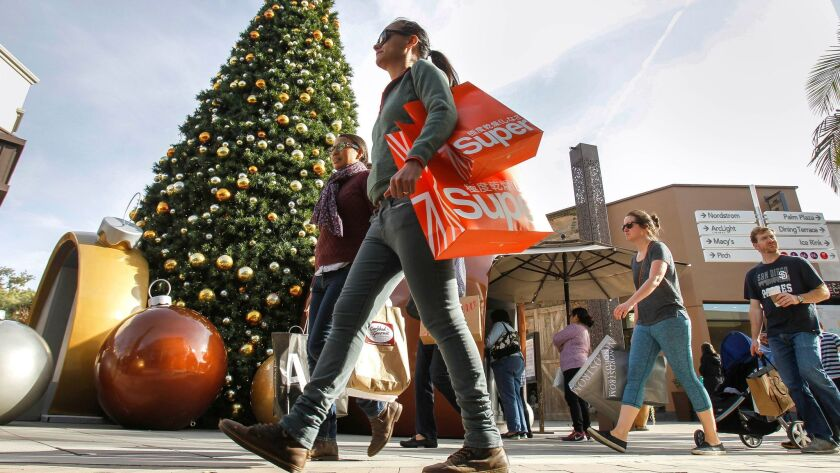 Many holiday retail jobs went away in Januray. Pictured: People walk past a Christmas tree at the Westfield UTC shopping mall as they shop there in San Diego on Saturday.