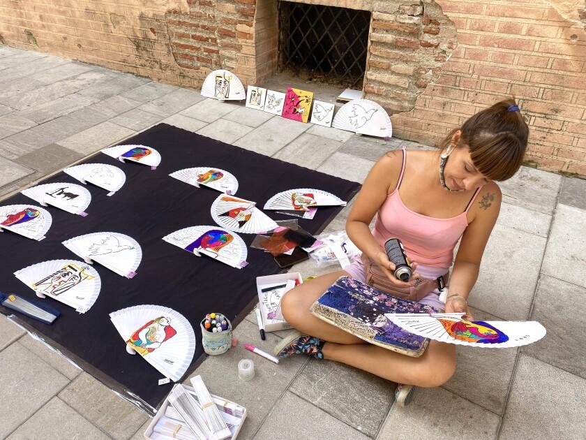 Mujer sentada en el suelo mientras hace ventiladores para souvenirs