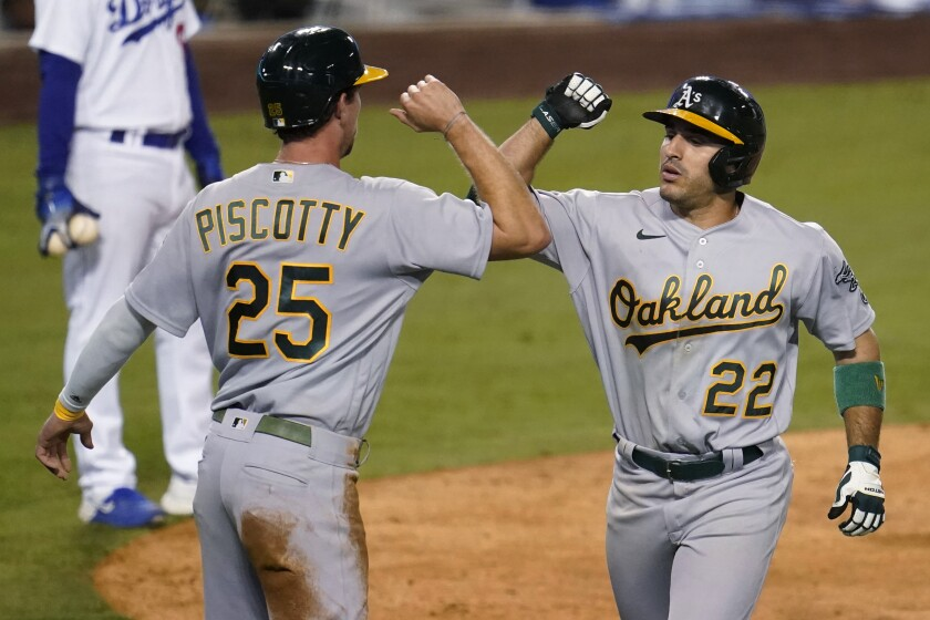 Oakland Athletics' Ramon Laureano, right, celebrates his two-run home run with Stephen Piscotty (25) during the ninth inning of the team's baseball game against the Los Angeles Dodgers on Wednesday, Sept. 23, 2020, in Los Angeles. (AP Photo/Marcio Jose Sanchez)
