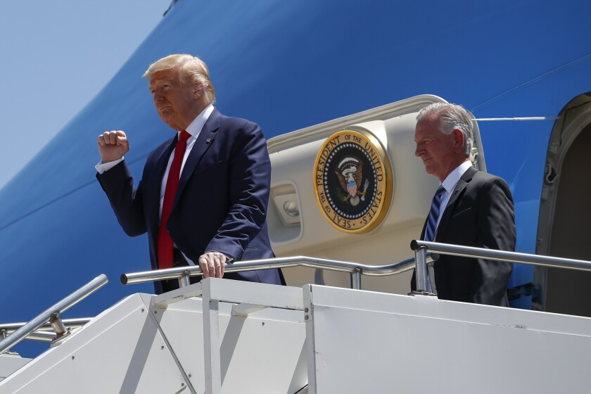 """FILE - In this June 11, 2020, file photo President Donald Trump gestures as he steps off Air Force One at Dallas Love Field in Dallas with Senate candidate Tommy Tuberville. Trump has endorsed Tuberville in the race, turning decisively against his former attorney general with direct appeals for Alabama voters to reject Sessions's candidacy. """"Do not trust Jeff Sessions,"""" Trump tweeted this spring. """"He let our Country down."""" (AP Photo/Alex Brandon, File)"""