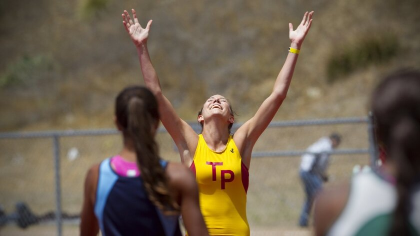 Torrey Pines senior Taylor Larch-Miller raises her hands in triumph after scoring a close win in the 100-meter hurdles over Devin Collins of Granite Hills (foreground).