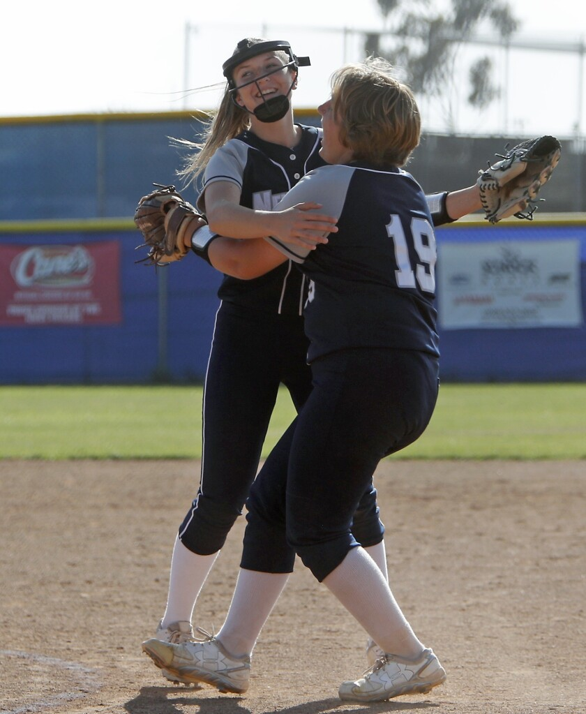 Newport Harbor High starting pitcher Clare Austin, right, shares a hug with closer McKayla Cotton af