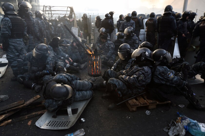 Riot police take a break near Kiev's Independence Square Wednesday afternoon after two days of clashes with the opposition.