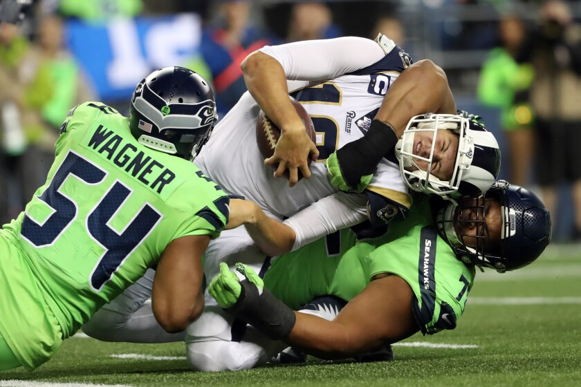 Rams quarterback Jared Goff is tackled by Seattle's Bobby Wagner, left, and Al Woods.