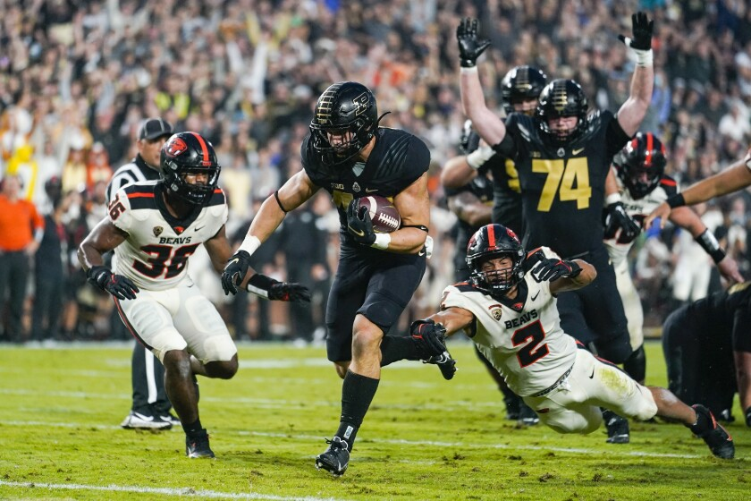 Purdue running back Zander Horvath (40) runs past Oregon State linebacker Andrzej Hughes-Murray (2) for a touchdown during the first half of an NCAA college football game in West Lafayette, Ind., Saturday, Sept. 4, 2021. (AP Photo/Michael Conroy)