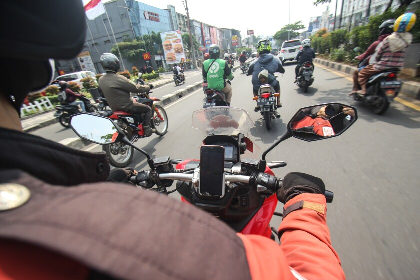 A motorcyclist rides while following others on their motorbikes.