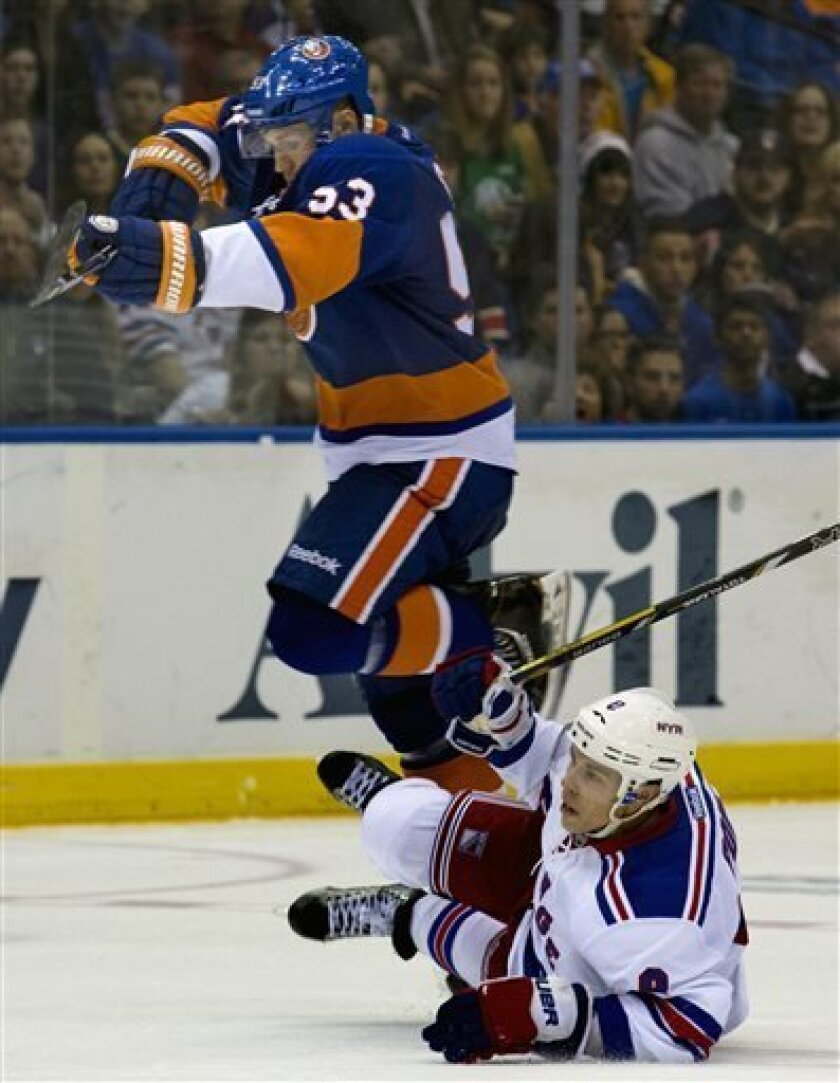 New York Islanders' Casey Cizikas, top, goes over New York Rangers' Darroll Payne in the third period of an NHL hockey game in Uniondale, N.Y. Saturday, April 13, 2013. The Rangers won 1-0 in overtime. (AP Photo/Craig Ruttle)