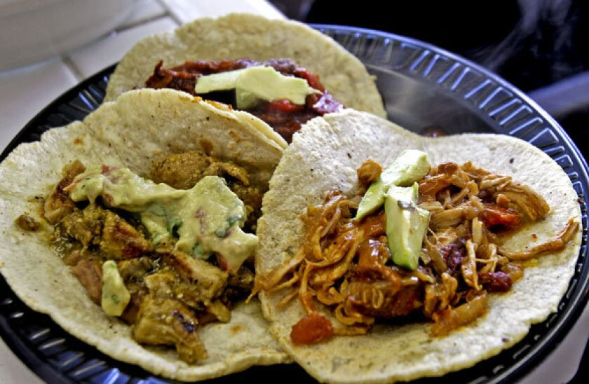 Pork in salsa verde, left, beef steak in pimento, rear, and tinga chicken are served on freshly made tortillas.