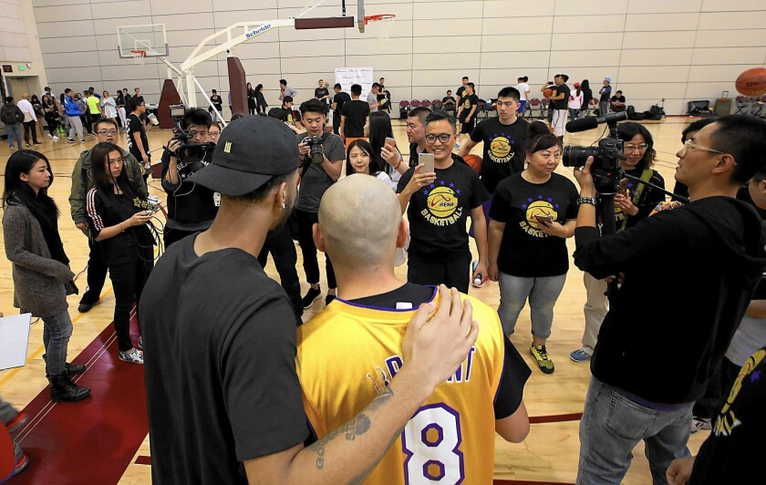 Members of a Chinese tour group in L.A. to watch Kobe Bryant's last NBA game pose for pictures with Lakers guard D'Angelo Russell at an event Tuesday at USC.