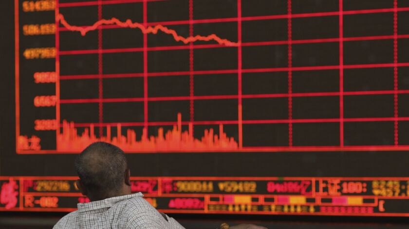 A Chinese investor watches as the Shanghai Composite Index falls at a brokerage in Beijing on Monday after President Trump's threat of more China tariffs.
