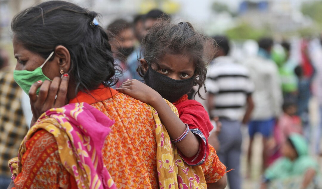 A woman carries a child as they wait with other migrant worker families to have their temperatures checked in Jammu, India.
