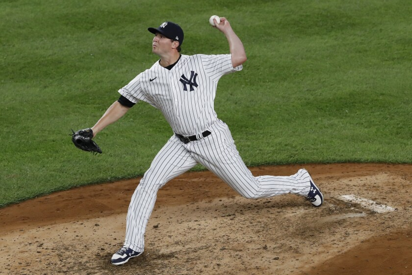 FILE - In this Aug. 3, 2020, file photo, New York Yankees relief pitcher Zack Britton winds up during the ninth inning of the team's baseball game against the Philadelphia Phillies at Yankee Stadium in New York. The Yankees plan to plan to exercise two option years on Britton worth $27 million and to decline options on outfielder Brett Gardner and pitcher J.A. Happ. The decisions were disclosed by a person familiar with the team's decisions who spoke on the condition of anonymity Thursday, Oct. 29, because they had not been announced. (AP Photo/Kathy Willens, File)