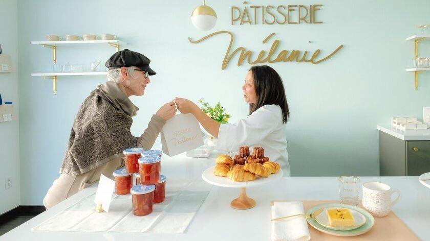 Melanie Dunn, owner of Pâtisserie Mélanie in Hillcrest, serves customer Rocio Weiss in the super-chic shop. Dunn, a former high school English teacher, said when she was making lists of what she might want to do next, she kept coming back to baking and pastry.