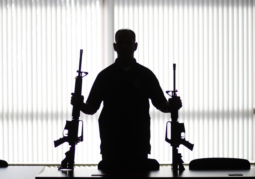 An ATF agent displays homemade rifles, or 'ghost guns,' at a field office in Glendale in 2017.