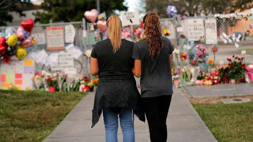 A mother and her daughter visit a makeshift memorial to shooting victims at the Marjory Stoneman Douglas High School in Parkland, Fla., on Feb. 19, 2018.