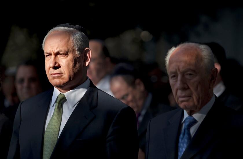 Benjamin Netanyahu stands next to Shimon Peres.