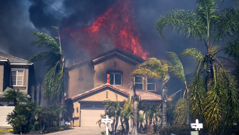 A home burns on Canyon Heights Dr in Anaheim Hills Monday afternoon after embers from the Canyon Fir
