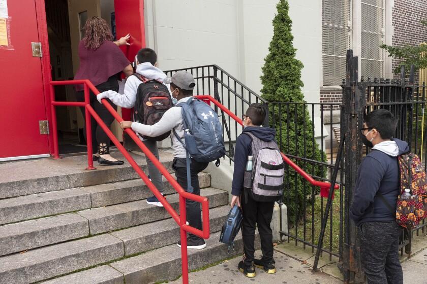 Una profesora conduce a sus estudiantes hacia el interior de una escuela primaria de Brooklyn