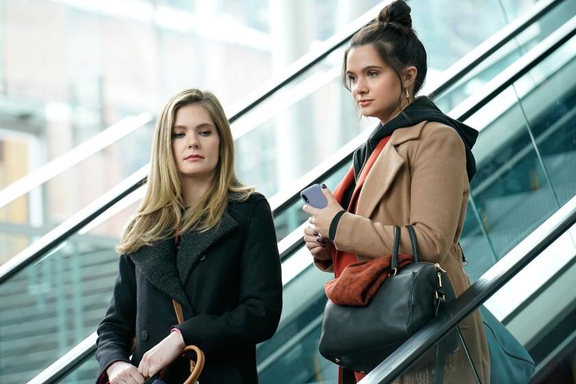Two women descend on an escalator.