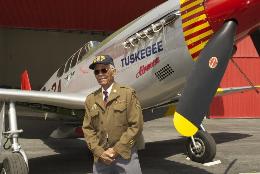 """This April 7, 2011 photo by Bruce Talamon shows Clarence E. """"Buddy"""" Huntley Jr., a member of the Tuskegee Airmen, the famed all-black squadron that flew in World War II, posing with a P-51C Mustang fighter plane similar to the one that he was a crew chief on while overseas during the war, at Torran"""