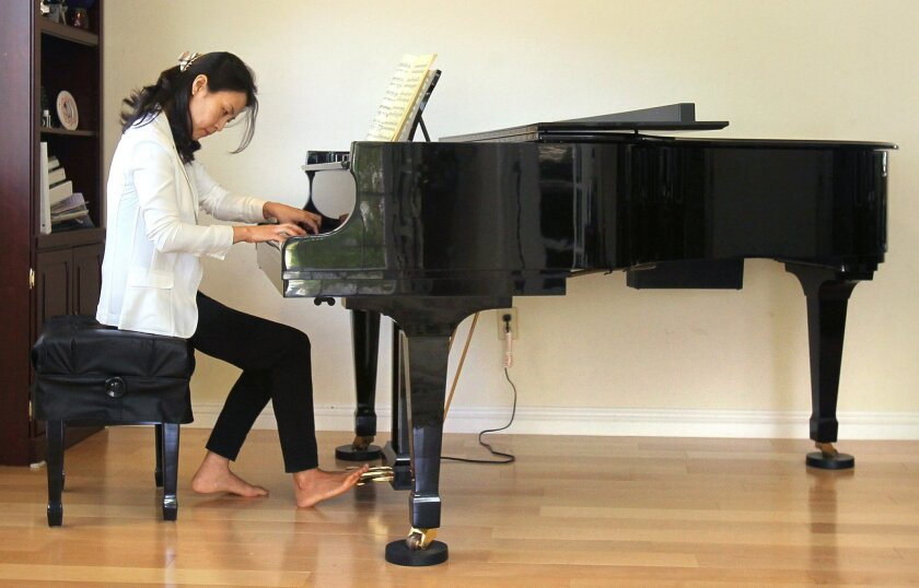 Cho Hyun Park practices on the piano at her Rancho Bernardo home.