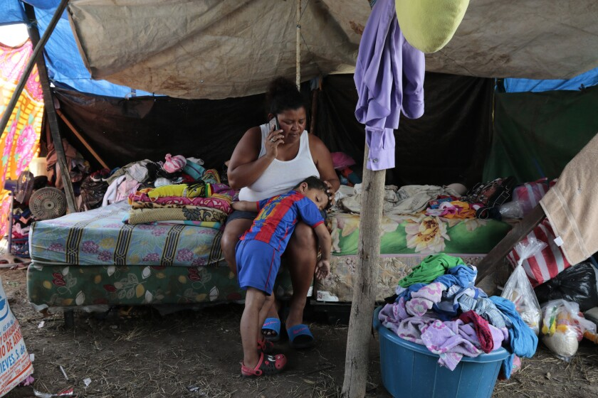 Wendy Guadalupe Contreras, who lost her Honduras home to Hurricane Eta, speaks on the phone while comforting her son.