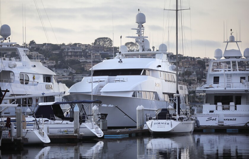The 145-foot superyacht Dumb Luck, center, is docked in Shelter Island basin.