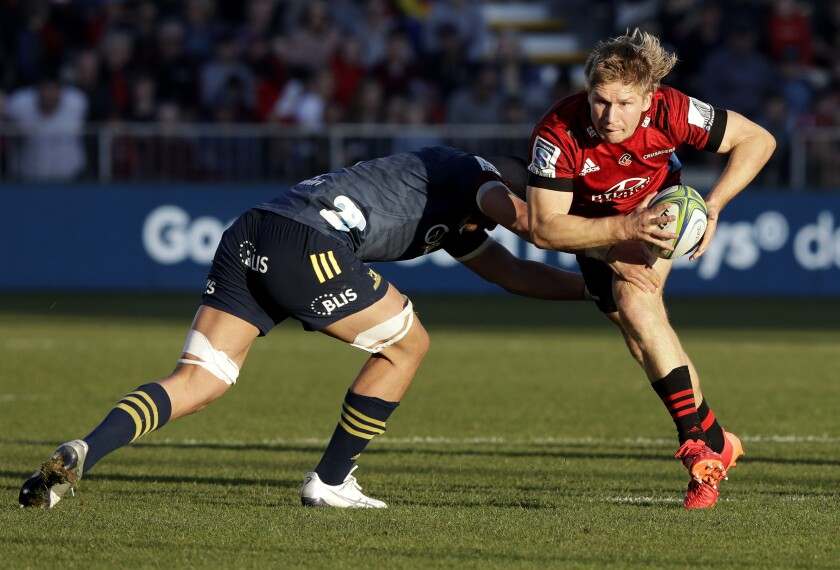 Crusaders Jack Goodhue, right, attempts to break the tackle of Highlanders Marino Mikaele-Tu'u during the Super Rugby Aotearoa rugby game between the Crusaders and the Highlanders in Christchurch, New Zealand, Sunday, Aug. 9, 2020. (AP Photo/Mark Baker)