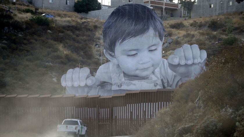 HOLD FOR STORY A Border Patrol vehicle drives in front of a mural in Tecate, Mexico, just beyond a b