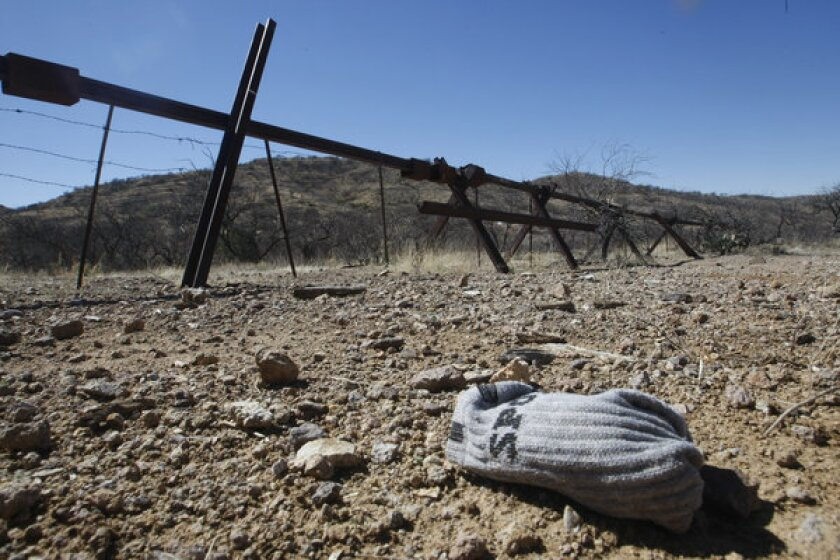 A pair of socks dropped by a migrant lies on the Arizona side of the U.S./Mexico border fence. Border Patrol agents patrolling the southern Arizona desert rescued 177 people in the last 30 days as temperatures soared to dangerous levels.