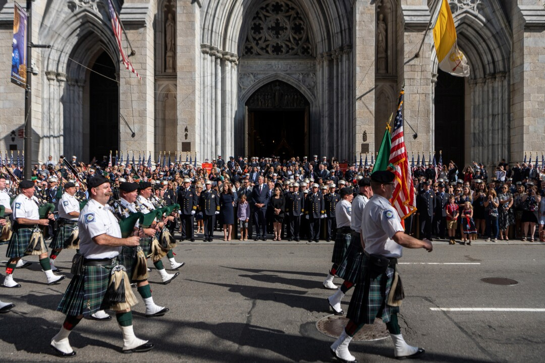 The FDNY Pipes and Drums marches past people at St. Patrick's Cathedral.