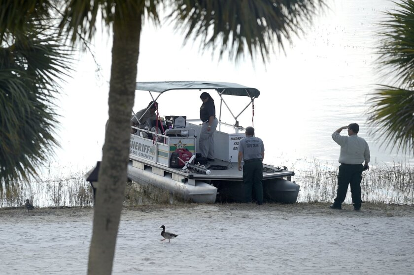FILE- In this June 15, 2016 file photo, law enforcement officials search the Seven Seas Lagoon outside the Grand Floridian Resort & Spa in Lake Buena Vista, Fla., after Lane Graves, a two-year-old toddler, was dragged into the lake by an alligator. Matt and Melissa Graves of Omaha, Nebraska, said i