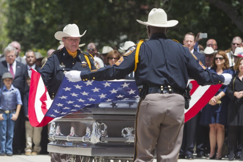 Members of the Harris County Sheriff's Office Honor Guard fold the flag that draped the casket during Deputy Darren Goforth's funeral in Houston.