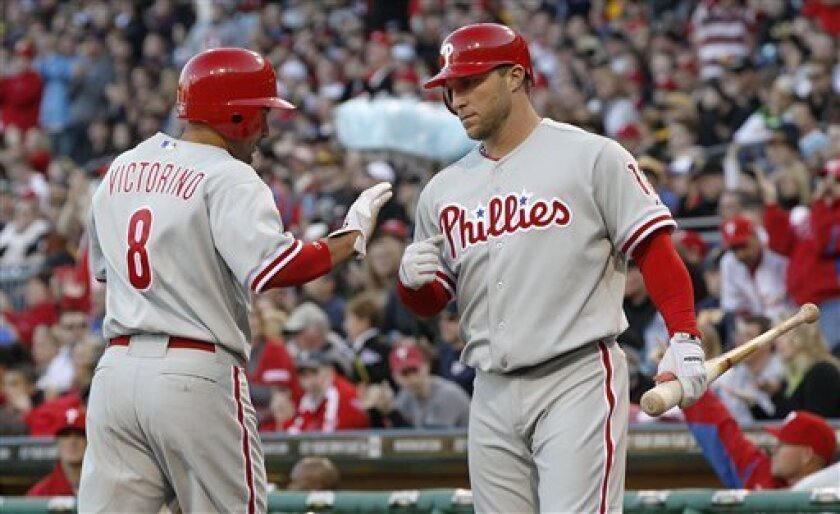 Philadelphia Phillies' Shane Victorino (8) is greeted by on-deck batter Philadelphia Phillies' Laynce Nix (19) after scoring in the first inning of the baseball game against the Pittsburgh Pirates, Saturday, April 7, 2012, in Pittsburgh. (AP Photo/Keith Srakocic)