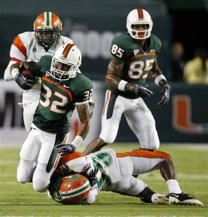 Miami's Lee Chambers (32) is tackled by Florida A&M's Fabian Wilson (38) after a first-down run during the second quarter of an NCAA college football game Saturday, Oct. 10, 2009, in Miami. (AP Photo/Hans Deryk)
