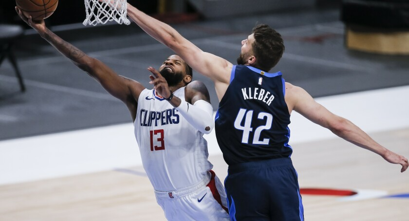 Los Angeles Clippers guard Paul George (13) attempts a layup as Dallas Mavericks forward Maxi Kleber (42) defends during the second half of an NBA basketball game, Monday, March 15, 2021, in Dallas. (AP Photo/Brandon Wade)