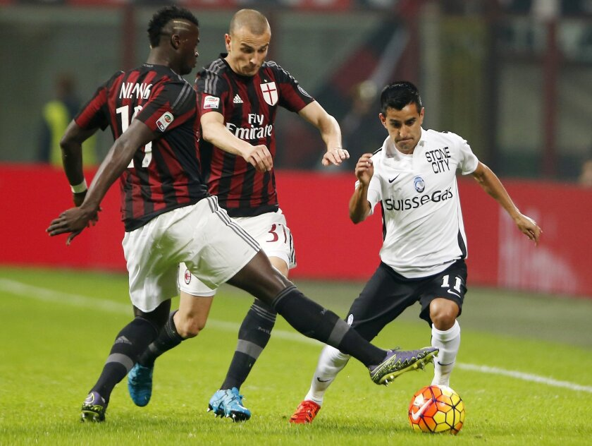 Atalanta's Maxi Moralez, right, challenges for the ball with AC Milan's Mbaye Niang, left, and AC Milan's Luca Antonelli during a Serie A soccer match at the San Siro stadium in Milan, Italy, Saturday, Nov. 7, 2015. (AP Photo/Antonio Calanni)