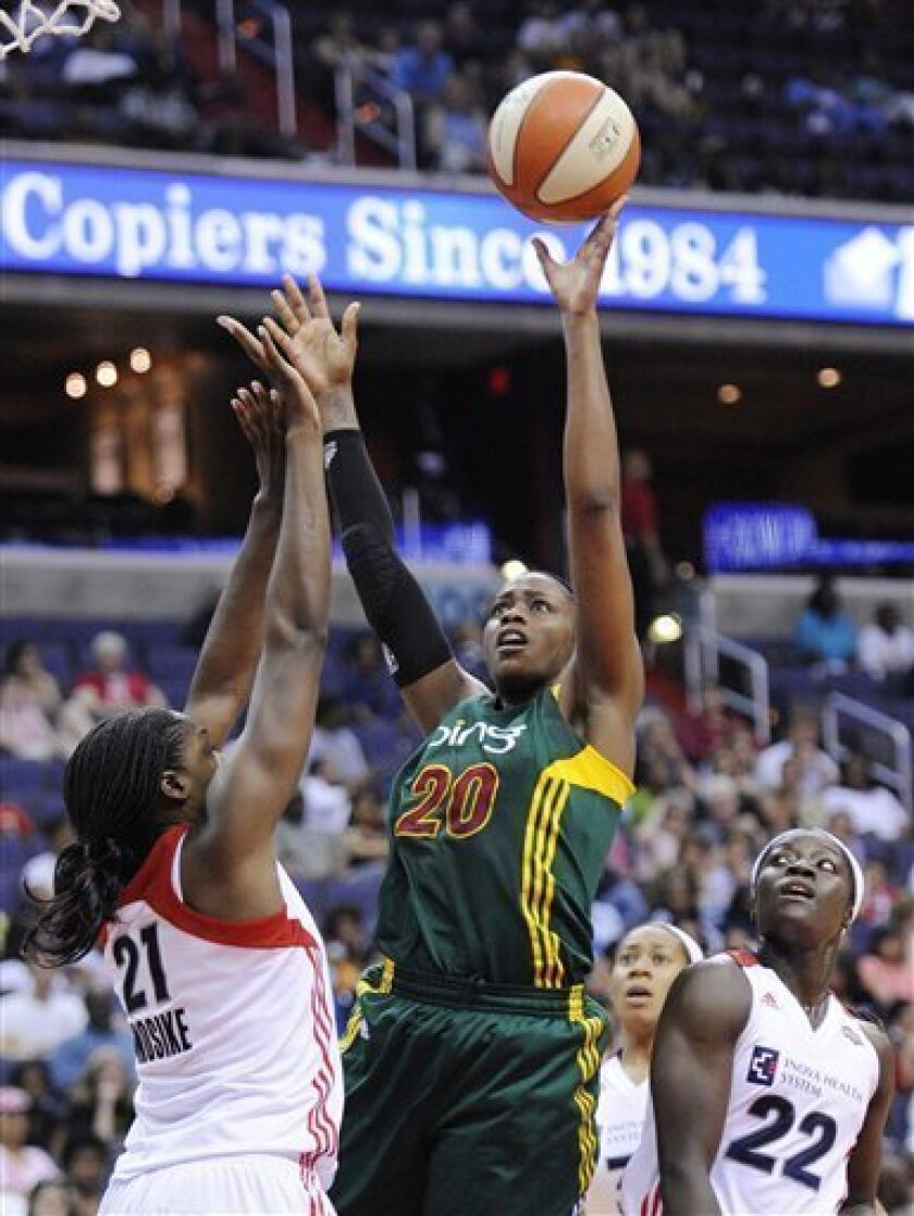 Seattle Storm's Camille Little (20) goes to the basket against Washington Mystics' Nicky Anosike (21) and Matee Ajavon (22) during the first half of an WNBA basketball game on Sunday, July 3, 2011, in Washington. (AP Photo/Nick Wass)
